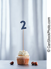 Minimalistic birthday cupcake with number 2 two