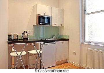 Minimalistic kitchen interior with small fridge and stove
