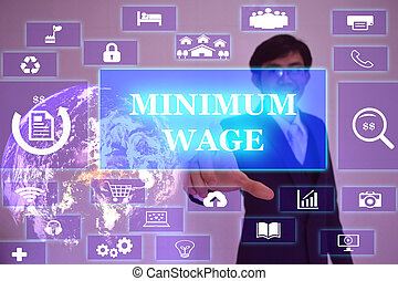 MINIMUM WAGE concept presented by businessman touching on...