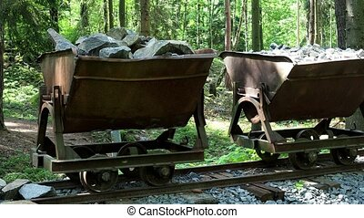 Mining cart with stones. Old and abandoned mining cart in...