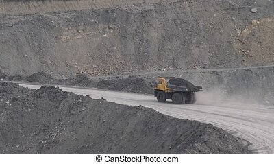 Mining dump trucks in the open pit mine. Loaded truck rides on the road quarry. The truck in the course of work.