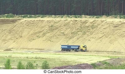 Mining for surface mining extraction of building yellow sand, devastation and degradation, a truck with a trailer transport the extracted sand