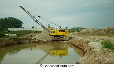 Mining for gravel sand pit excavator or digger machine dredger extraction colliery output of building surface gray pile and mine quarry grit quartz pea ballast road-metal, high quality industry building material, hole devastation of nature and landscape, construstion site, global change, degradation...
