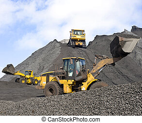 Three huge shovels at work in a large coal field