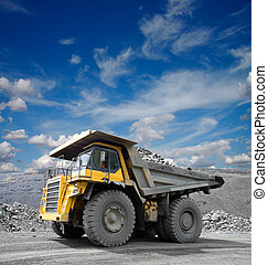 Heavy mining truck driving through the iron ore opencast