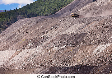 Mining truck on haul road at tailings hill side - Big mining...