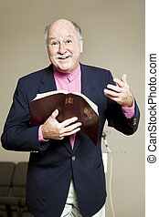 Minister holding a bible and preaching a positive, inspiring sermon.