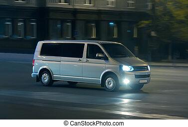 Minivan moves at night on a city street