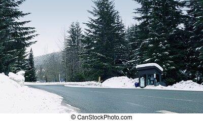 Minivan Passes Bus Shelter In Snow - Minivan drives past bus...