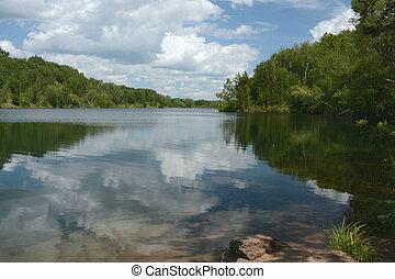 Placid summer reflections on scenic Pennington Mine Lake in central Minnesota.