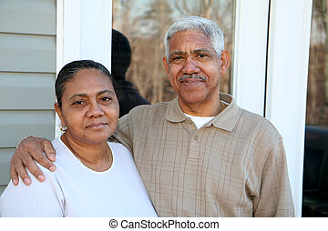 Minority Couple - Minority couple standing in front of their...