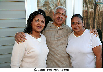 Minority Family - Minority family standing outside their new...