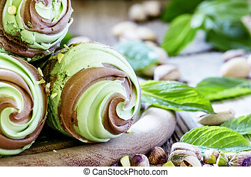 Mint-chocolate ice cream with pistachios in a waffle cone, vintage wooden background, selective focus