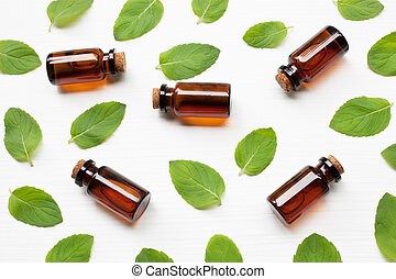 Mint Essential Oil in a Glass Bottle with leaves.