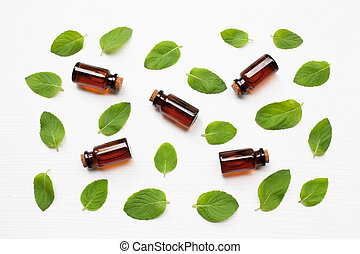 Mint Essential Oil in a Glass Bottle with leaves on white background.