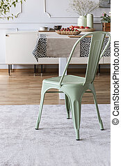 Mint green chair on grey carpet at table in rustic dining room interior with lamp and wall with molding. Real photo
