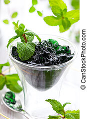 Mint jelly in glass with spoon and fresh mint leaves
