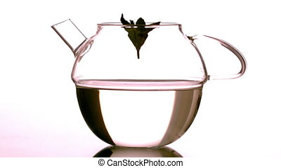 Mint leaf falling into glass teapot in slow motion