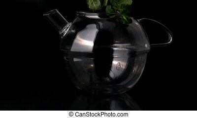 Mint leaves falling into glass teapot in slow motion