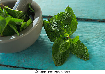 Mint leaves with mortar and pestle on wooden table