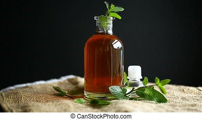 Mint syrup in a glass bottle on a black background