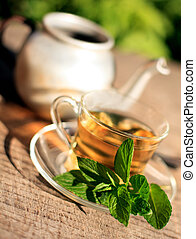 mint tea - cups of tea with mint on soft focused green ...