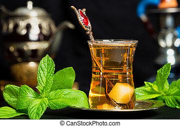 Mint tea - traditional Arabian drink on black backgroun