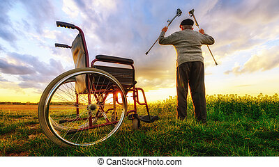 Miracle recovery: Old man gets up from wheelchair and raises hands up. Shot in a meadow.