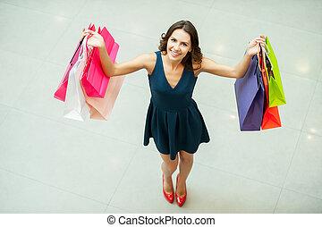 mirada, qué, yo, get!, punta la vista, de, hermoso, mujer joven, tenencia, bolsas de compras, y, sonriente, en cámara del juez