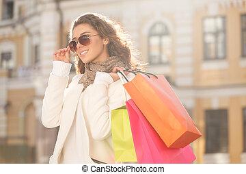 miradas, grande, con, ella, nuevo, sunglasses., hermoso, mujeres jóvenes, en, gafas de sol, tenencia, el, bolsas de compras, y, el mirar lejos