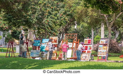 Miraflores central park timelapse. Place for relax with green trees and lawn in Peruvian capital. Artists selling paintings. People sitting on benches and walking around. Lima, Peru