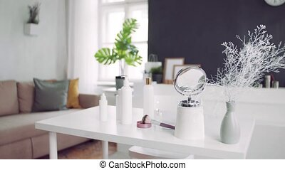 Mirror and beauty products on the desk. - A mirror and ...