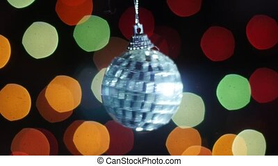 Mirror ball rotates at background of bokeh lights