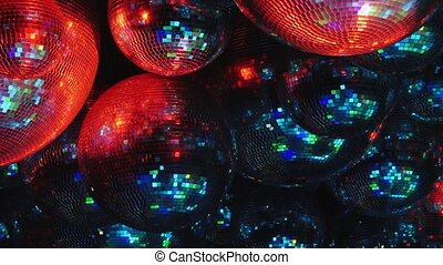 Mirror balls reflect rays of colored lights.