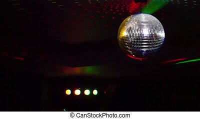 Mirror balls rotate and reflect lights of projectors breaking through smoke at night club