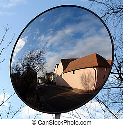 Mirror Blue - A village street and houses reflected in a...