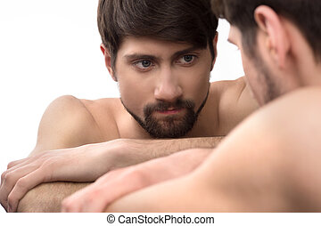 Mirror image. Young man looks at himself in the mirror