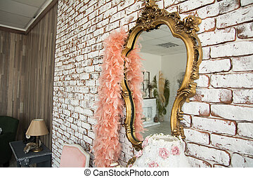 Mirror in golden curly frame against