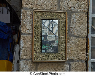Mirror on the wall of old building in the medina of Jerusalem, Israel.