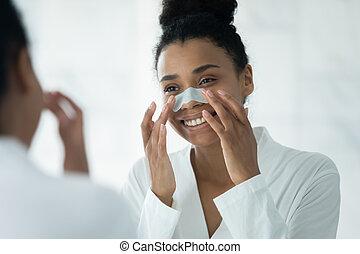 Mirror reflection African American woman applying anti blackhead patch