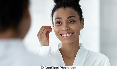Mirror reflection African American woman cleaning ears, using cotton bud