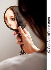 Closeup of a mirror reflection of a woman's eye, selective focus