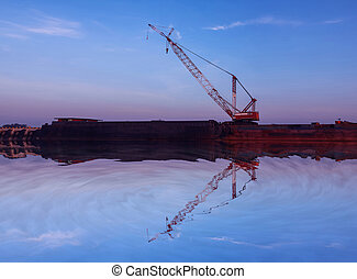 Mirror reflection of Crawler cranes used for rebuilding bridges near the river