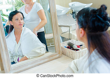 Mirror reflection of lady having hair styled