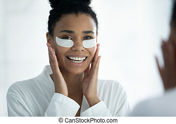 Mirror reflection smiling African American woman applying hydrogel eye patches