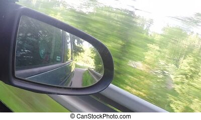 Mirror view from car driving in spring countryside