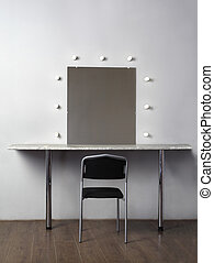 mirror with lamps for makeup, black chair in studio, white wall