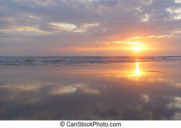 Sunset at a beach with clouds mirrored at the beach