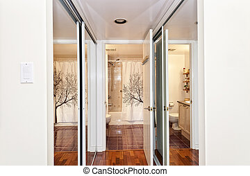 Mirrored closets and bathroom - Interior hallway with walk...