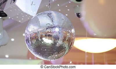 Mirrored disco ball in a white glow of reflected rays. Close up